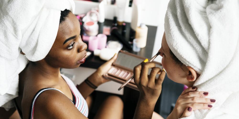 Woman applying makeup on her friend