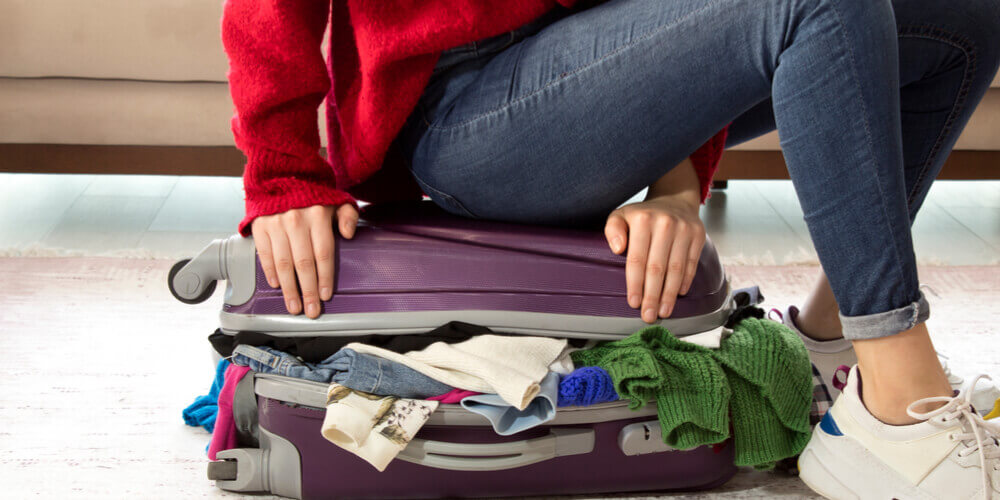 Woman sitting on suitcase trying to get everything to fit
