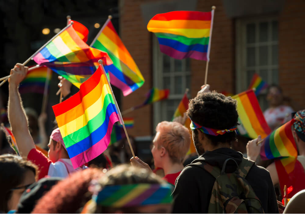 A large crowd of people celebrating pride with rainbow flags