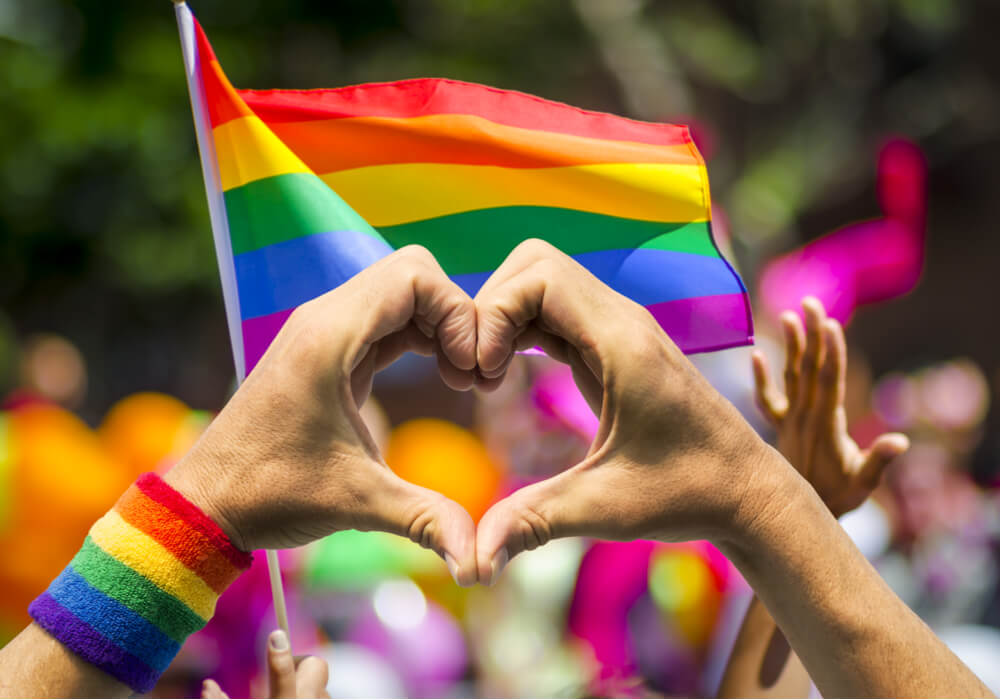 Hands making a heart shape in front of a rainbow flag to celebrate Pride