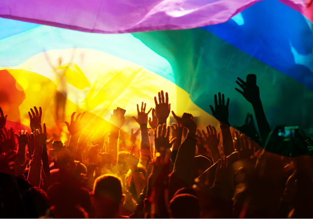 A large crowd of people dancing and celebrating Pride underneath a big rainbow flag