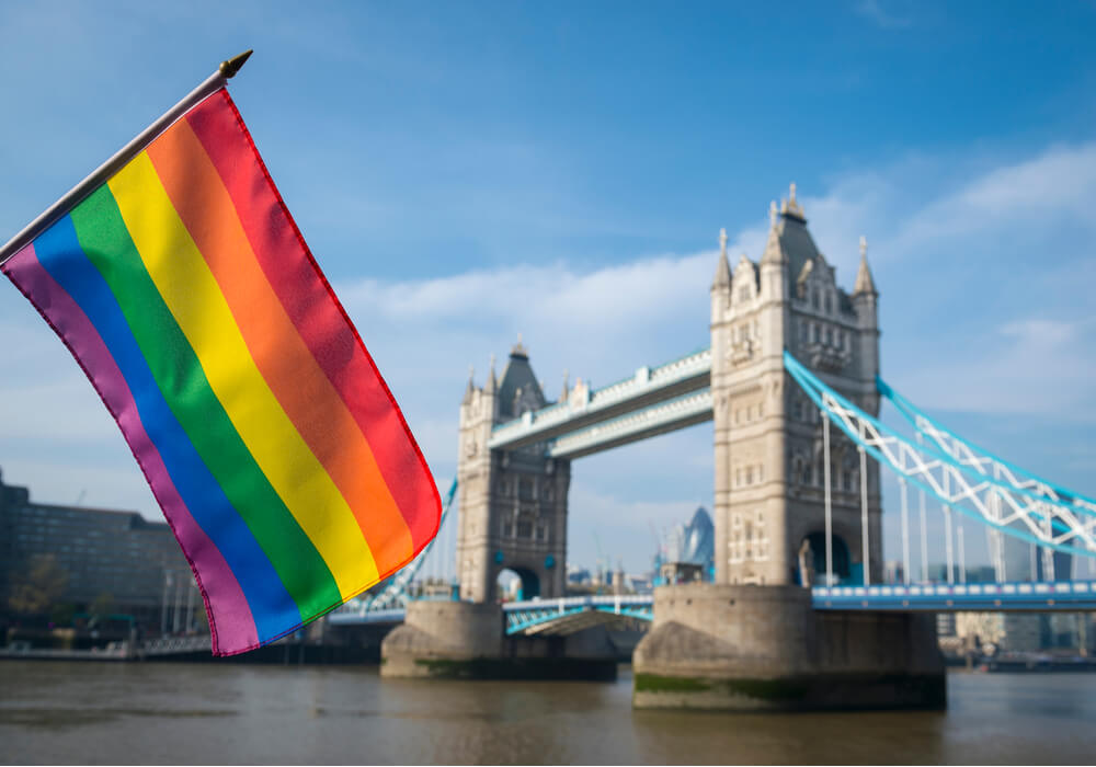 Pride rainbow flag in front of London skyline at Tower Bridge on a summer day