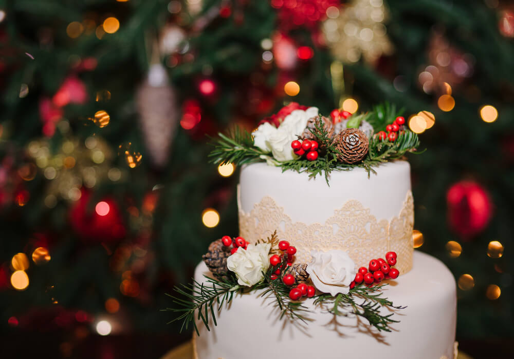 White wedding cake at a Christmas themed wedding with Christmas tree and bright lights in the background