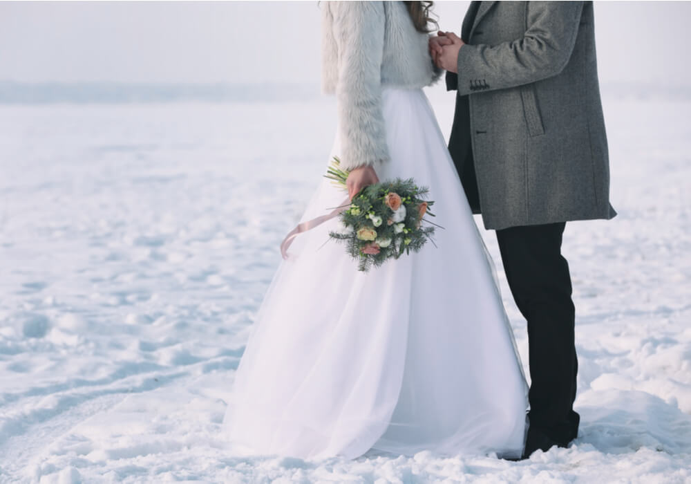 Bride and Groom in the snow at their winter wedding