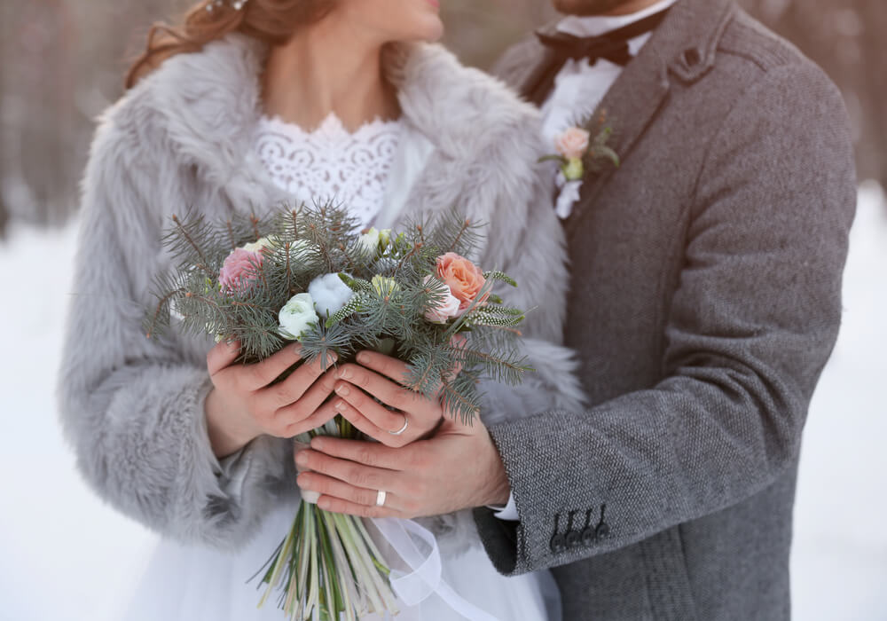 Bride in a faux fur jacket with her groom and a winter bouquet