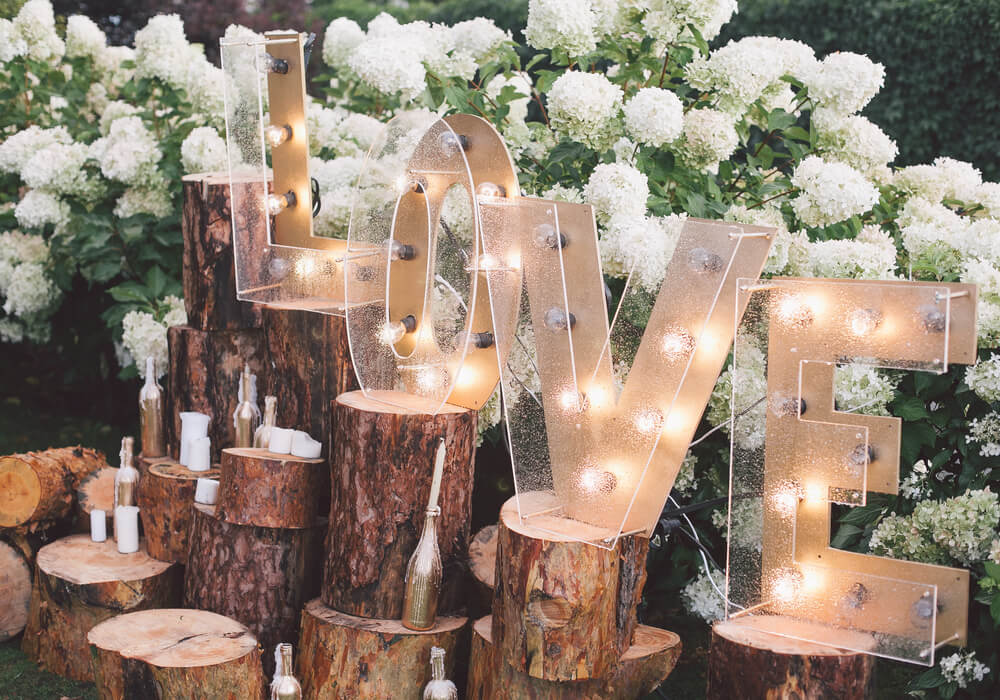Love sign at a wedding with greenery and candles