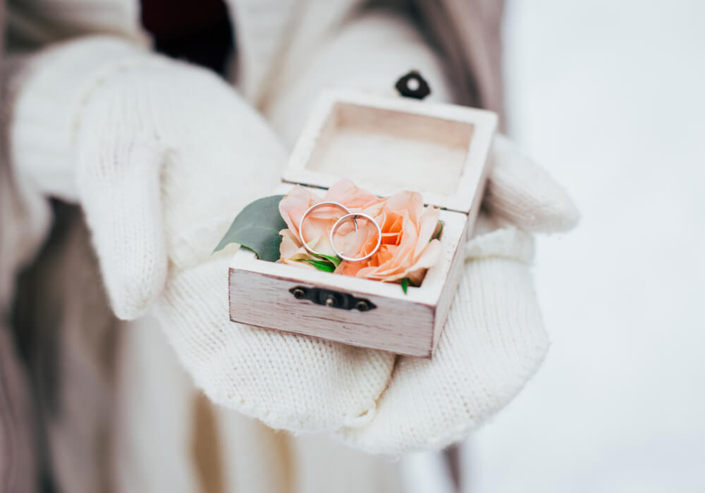 Gloved hands holding wedding rings at a winter wedding