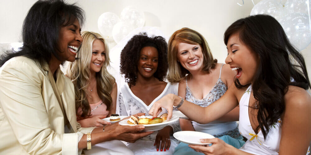 Group of women laughing and eating dessert at a Kitchen Tea party