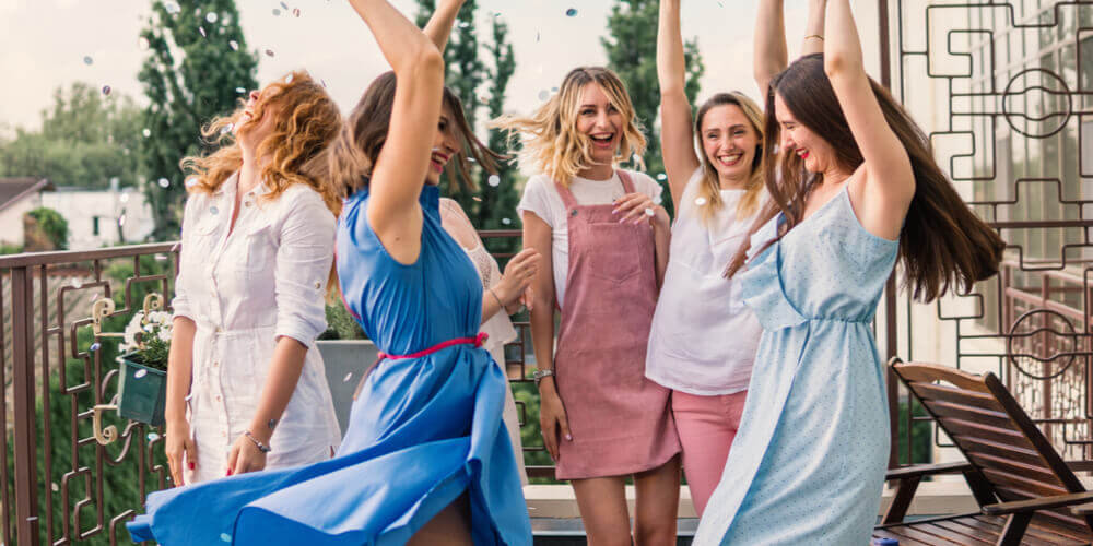 women on a hen party dancing on a terrace with confetti in the air