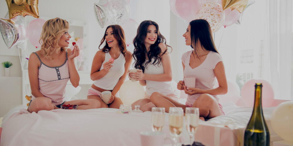 women on a hen party talking and eating snacks and drinking with decorations in the background