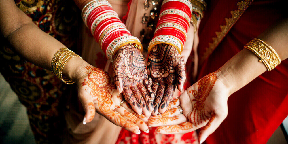 Indian bride and bridesmaids with mehndi/henna design on their hands